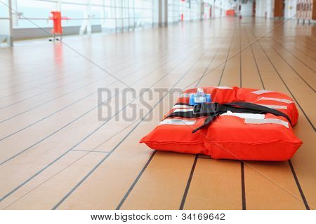 Singular orange life jacket lies on deck of cruise passenger liner