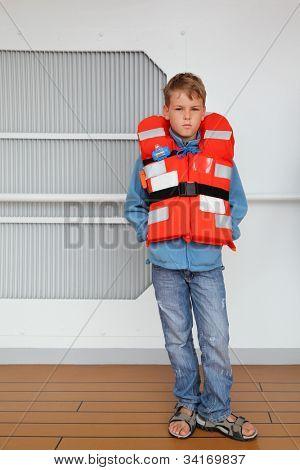 Sério rapaz vestindo de colete laranja fica no convés do navio.