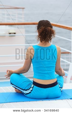 back of young woman wearing in sports suit sitting on cruise liner deck and meditating