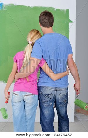 happy young couple paint in green and blue color white wall of their new home