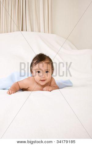 Étnicos menino deitado no cobertor