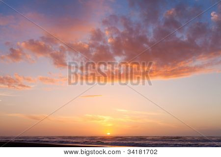 Colorful sunset cloudscape over beach and ocean