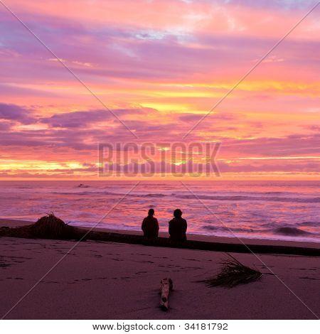 Romantic couple enjoy spectacular beach sunset