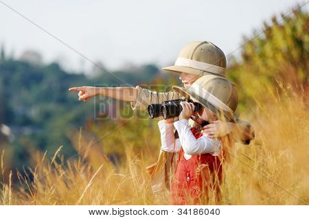 Happy young safari adventure children playing outdoors in the grass with binoculars and exploring together as brother and sister.