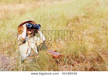 Young boy plays safari explorer with binoculars and bush hat in a field. happy adventure seeking kid playing outdoors.