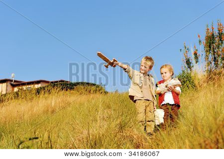 Young children playing explorers with treasure map and wooden sword. little adventure seeking kids having fun outdoors in the back yard