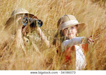 Crianças de aventura safari jovem feliz jogando ao ar livre na grama com binóculos e explorar a