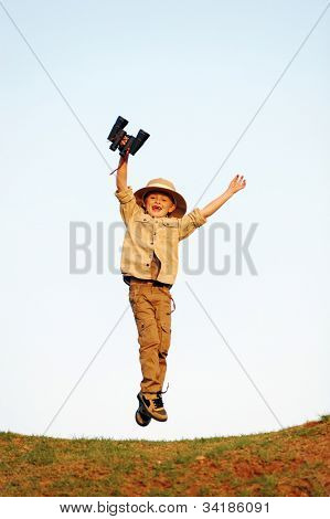 Jumping child explorer with binoculars and safari hat playing adventure games outdoors