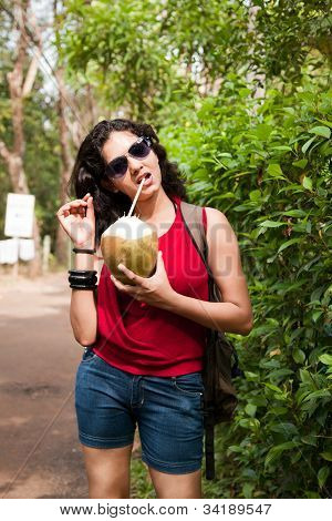 Indian young girl enjoying coconut water