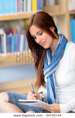 Female high school student at library writing into notepad