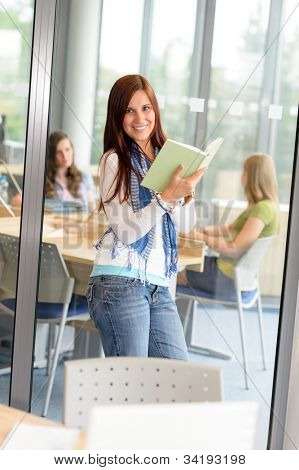 Female teenager student reading book at high school study room