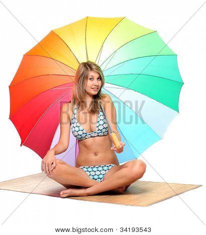 Junge Frau im Badeanzug ruhelosigkeit unter einem Sonnenschirm.