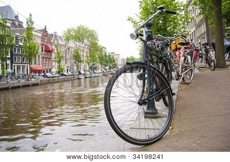 AMSTERDAM, HOLLAND - MAY 29: Detail of bicycle chained by canal in the city centre. May 29, 2012 in Amsterdam. It is estimated that there are about 550 thousand bikes in Amsterdam.