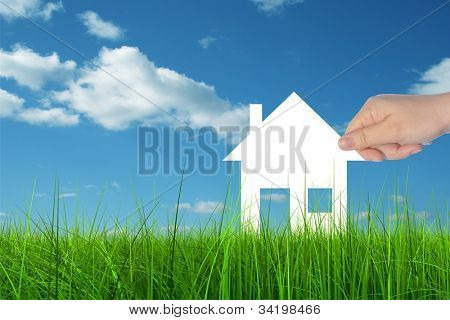 Concept or conceptual White paper house held in hand by a man in a green summer grass over a blue sky background with clouds, as a symbol for construction,eco,ecology,loan,mortgage,property or home