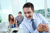 stock photo of cunning  - Cunning manager rubbing his hands while his unaware clients signing the contract - JPG