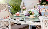 stock photo of fancy cakes  - Afternoon tea and cakes in the garden with wicker furniture - JPG
