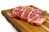 Raw Pork Steak On Wood Cutting Board. Pork With Spices: Rosemary And Pepper. Close-up Raw Pork Steak poster