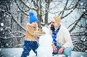 Merry Christmas And Happy New Year. Happy Father And Son Making Snowman In The Snow. Handmade Funny  poster