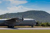 foto of c130  - c130 gunship with propeller in action about to take off - JPG