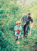 Planting Flowers. Growing Plants. Boy And Father In Nature With Watering Can And Shovel. Dad Teachin poster