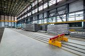 A Plant For The Production Of Hollow Floor Slabs With Indoor Equipment And New Panels Piled On A Pil poster