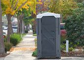 Port A Potty Sitting In A Driveway Next To The Sidewalk In A Neighborhood Tree Lined And Picturesque poster