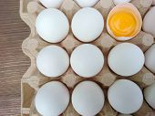White Eggs Carton & Cracked Egg Half With Yolk Top View On Wooden Background. Broken And Whole Eggs  poster