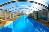Swimming Pool With Blue Water And Transparent Plastic Tent. Modern Pool Design With Collapsible Wall poster