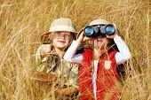 Happy young safari adventure children playing outdoors in the grass with binoculars and exploring to