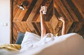 Lazy Female Lying Under The White Blanket On The  Linen Bed And Holding The Fresh Coffee Cup In The  poster