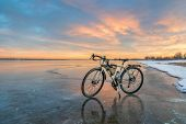 winter biking, touring or commuting - bicycle on an icy lake shore against sunset sky, Boyd Lake Sta poster