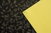 Yellow A4 Paper Bundled With A Paper Clip, On A Metallic Black Surface. Many Paper Clips Around. Cop poster