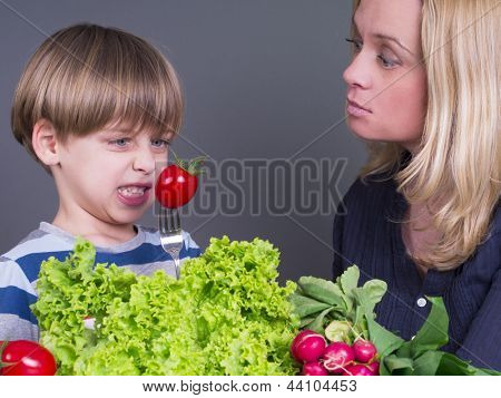 Mother with her son who resists eating tomato
