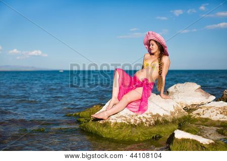 Happy Beautiful Pregnant Woman In Swimsuit Relaxing At Beach. The Concept Of Health And Rest
