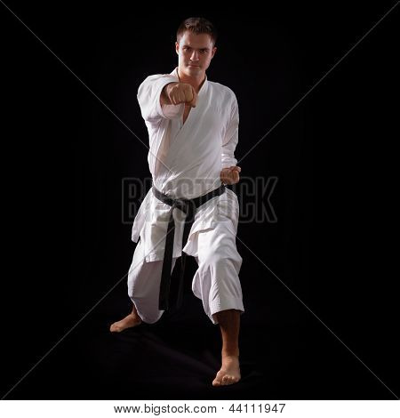 karate man with black belt posing, champion of the world on black background studio shot