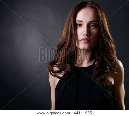 Young woman with beautiful long brown hair posing at studio, looking at camera, face closeup, over black background