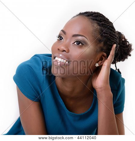 Beautiful young african woman dreaming and looking left into the corner, over white