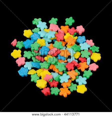 Flower-Shaped Colorful Sugar Sprinkles (Edible Cake Decorations) On Black Background