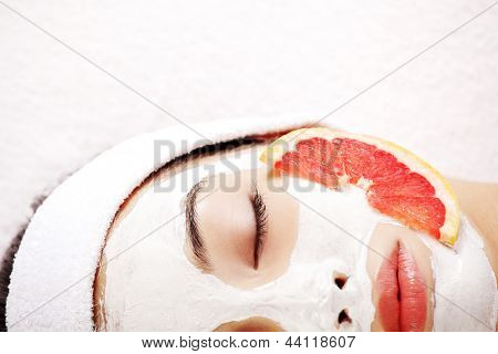 Attractive young woman with fruit mask on a face at spa saloon