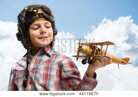 Boy in helmet pilot playing with a toy airplane
