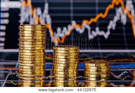 Down Trend Stacks Of Golden Coins And Financial Chart As The Background. Selective Focus