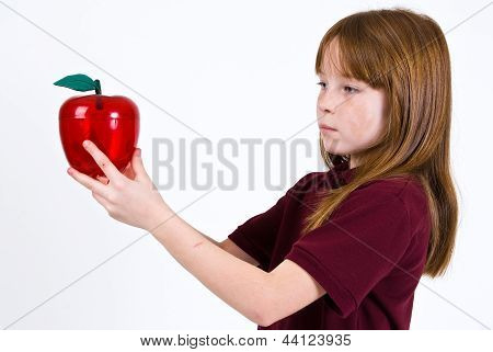 Female school child holding a clear plastic apple