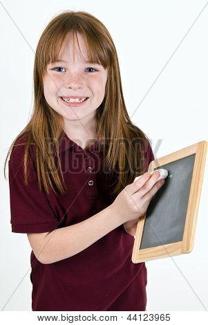 Young school girl writing on chalk board