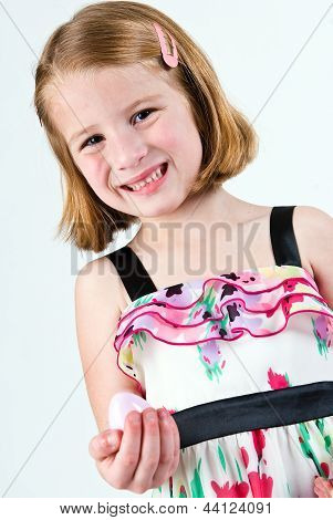 Young girl grimacing with plastic Easter egg