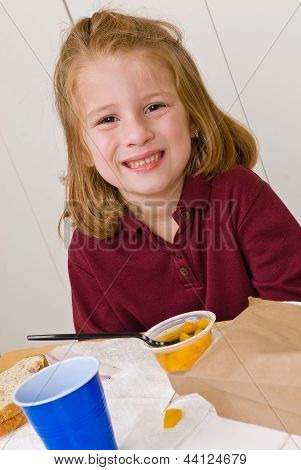 Young school girl smiling while eating lunch