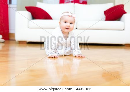 Happy Eight Month Old Baby Girl Crawling On A Hardwood Floor
