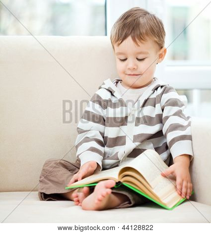 Little boy is reading book while sitting on couch, indoor shoot