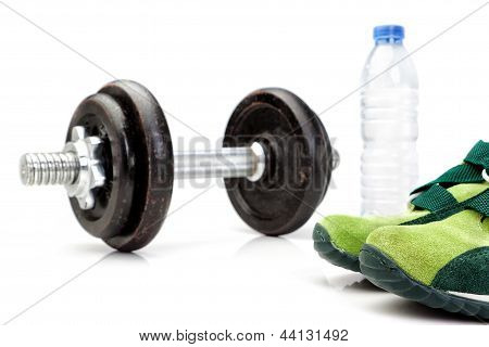 Dumbbell, A Bottle Of Pure Water In The Background And Running Shoes For Athletics.