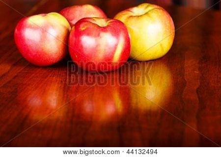 Red Apples On A Shiny Wood Table