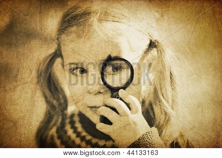 Girl looking through magnifier. Vintage styled shot